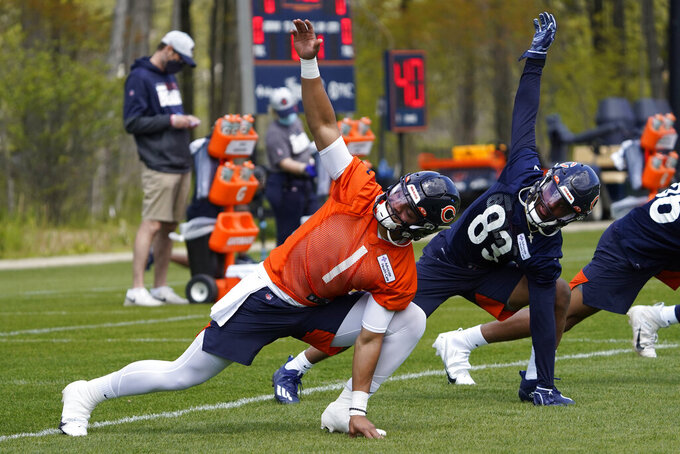Chicago Bears quarterback Justin Fields (1) and wide receiver Dazz Newsome (83) stretch during the NFL football team's rookie minicamp Friday, May, 14, 2021, in Lake Forest Ill. (AP Photo/David Banks, Pool)