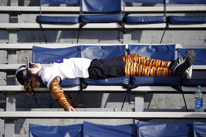 An LSU fan takes a nap during the second quarter of an NCAA college football game against Auburn, Saturday, Oct. 31, 2020, in Auburn, Ala. (AP Photo/Butch Dill)