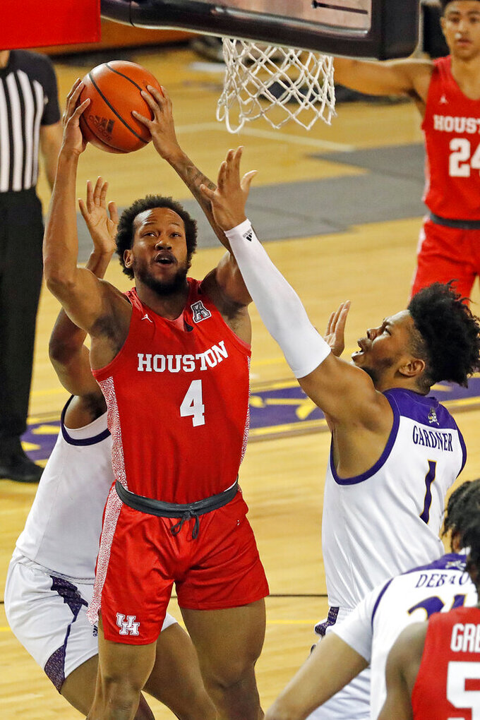 Houston's Justin Gorham (4) tries to score over East Carolina's Jayden Gardner (1) during the first half of an NCAA college basketball game in Greenville, N.C., Wednesday, Feb. 3, 2021. (AP Photo/Karl B DeBlaker)