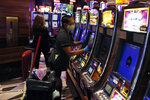 Casino worker Edith Smith-Meah sanitizes a video slot machine at the MGM Grand Detroit casino, Wednesday, Aug. 5, 2020, in Detroit. Detroit's three casinos will start reopening Wednesday under new governor-mandated capacity restrictions, four and a half months after closing for the coronavirus pandemic. MotorCity Casino Hotel and the Greektown Casino-Hotel. opened Wednesday. MGM Grand Detroit will open for invite-only VIP customers Wednesday and Thursday, and at 10 a.m. Friday for the general public. (AP Photo/Carlos Osorio)