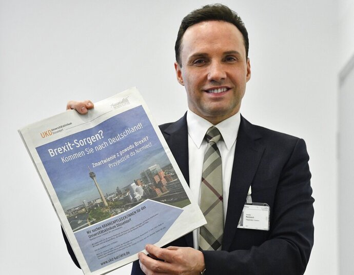In this Tuesday, Feb. 12, 2019 photo, the Director of Nursing Torsten Rantzsch poses with his advertisement in Polish newspapers in the UK, reading
