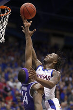 Kansas guard Marcus Garrett, right, shoots over Kansas State forward Makol Mawien (14) during the first half of an NCAA college basketball game in Lawrence, Kan., Tuesday, Jan. 21, 2020. (AP Photo/Orlin Wagner)