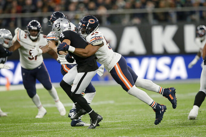 Chicago Bears outside linebacker Khalil Mack (52) tackles Oakland Raiders quarterback Derek Carr (4) during the second half of an NFL football game at Tottenham Hotspur Stadium, Sunday, Oct. 6, 2019, in London. (AP Photo/Tim Ireland)
