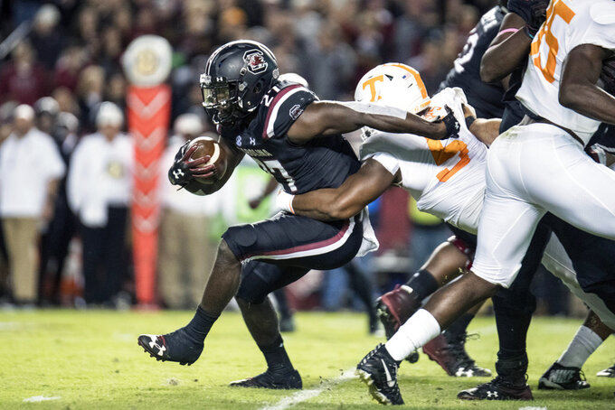 South Carolina running back Ty'Son Williams (27) is wrapped up by Tennessee defensive lineman Kyle Phillips (5) during the first half of an NCAA college football game Saturday, Oct. 27, 2018, in Columbia, S.C. (AP Photo/Sean Rayford)