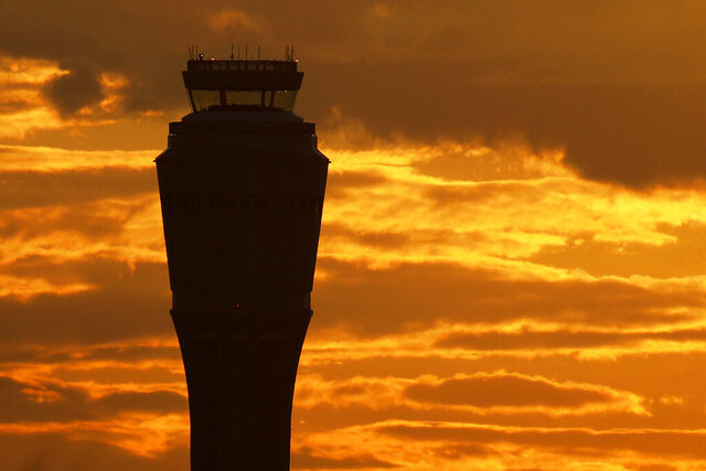 The sun rises behind the air traffic control tower at McCarran International airport, Thursday, March 19, 2020, in Las Vegas.  Officials at  the airport said in a tweet that it will remain open with reduced operations after an air traffic controller tested positive late Wednesday, temporarily closing the control tower. (AP Photo/John Locher)