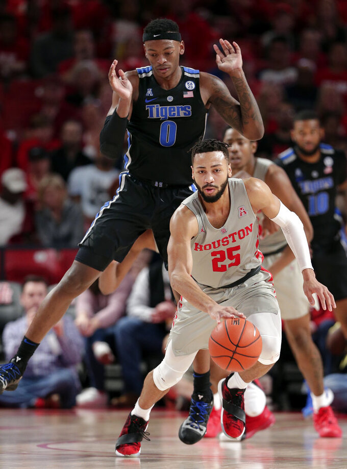 Houston guard Galen Robinson Jr. (25) brings the ball down court after a turnover as Memphis forward Kyvon Davenport (0) jumps to avoid the foul during the second half of an NCAA college basketball game Sunday, Jan. 6, 2019, in Houston. (AP Photo/Michael Wyke)