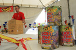 File - In this July 1, 2014, file photo, Nathan Farmer unpacks dozens of boxes of fireworks to sell at a roadside stand in Albuquerque, N.M. Albuquerque is joining a growing number of communities in California and Texas asking residents to use an app to report illegal fireworks on July 4th instead of calling 911. (AP Photo/Susan Montoya Bryan, File)