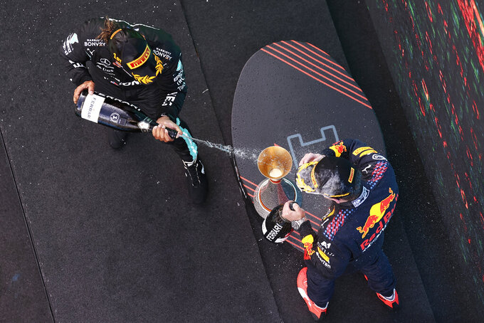 Winner Mercedes driver Lewis Hamilton of Britain sprays second placed Red Bull driver Max Verstappen of the Netherlands, right, on the podium of the Spanish Formula One Grand Prix at the Barcelona Catalunya racetrack in Montmelo, just outside Barcelona, Spain, Sunday, May 9, 2021. (Lars Baron/Pool via AP)