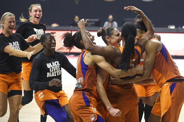 Phoenix Mercury guard Shey Peddy (5) is swarmed by teammates after Peddy scored the game-winning shot as time expired during a WNBA basketball first-round playoff game agains the Washington Mystics, Tuesday, Sept. 15, 2020, in Bradenton, Fla. (AP Photo/Phelan M. Ebenhack)
