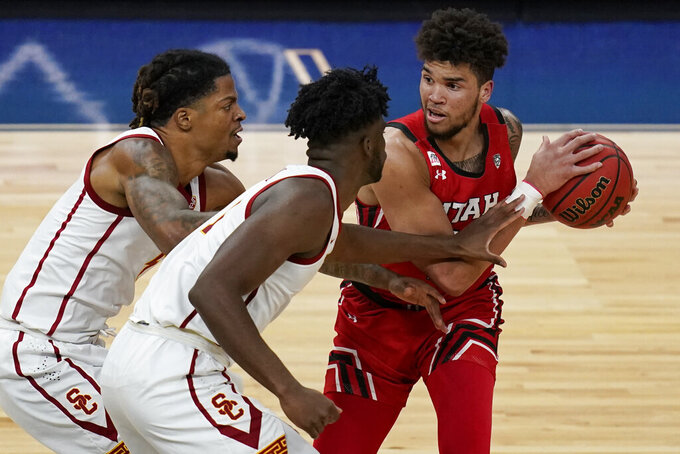 Utah's Timmy Allen (1) looks to pass around Southern California's Chevez Goodwin, center, and Isaiah White during the first half of an NCAA college basketball game in the quarterfinal round of the Pac-12 men's tournament Thursday, March 11, 2021, in Las Vegas. (AP Photo/John Locher)