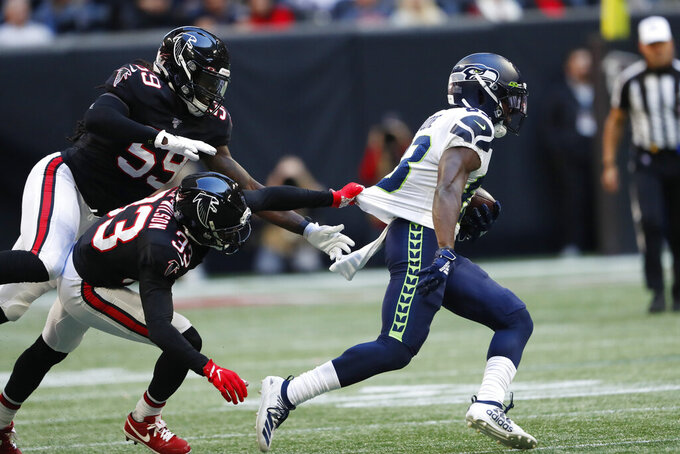 Atlanta Falcons defensive back Blidi Wreh-Wilson (33) misses the tackle on Seattle Seahawks wide receiver David Moore (83) during the second half of an NFL football game, Sunday, Oct. 27, 2019, in Atlanta. (AP Photo/John Bazemore)