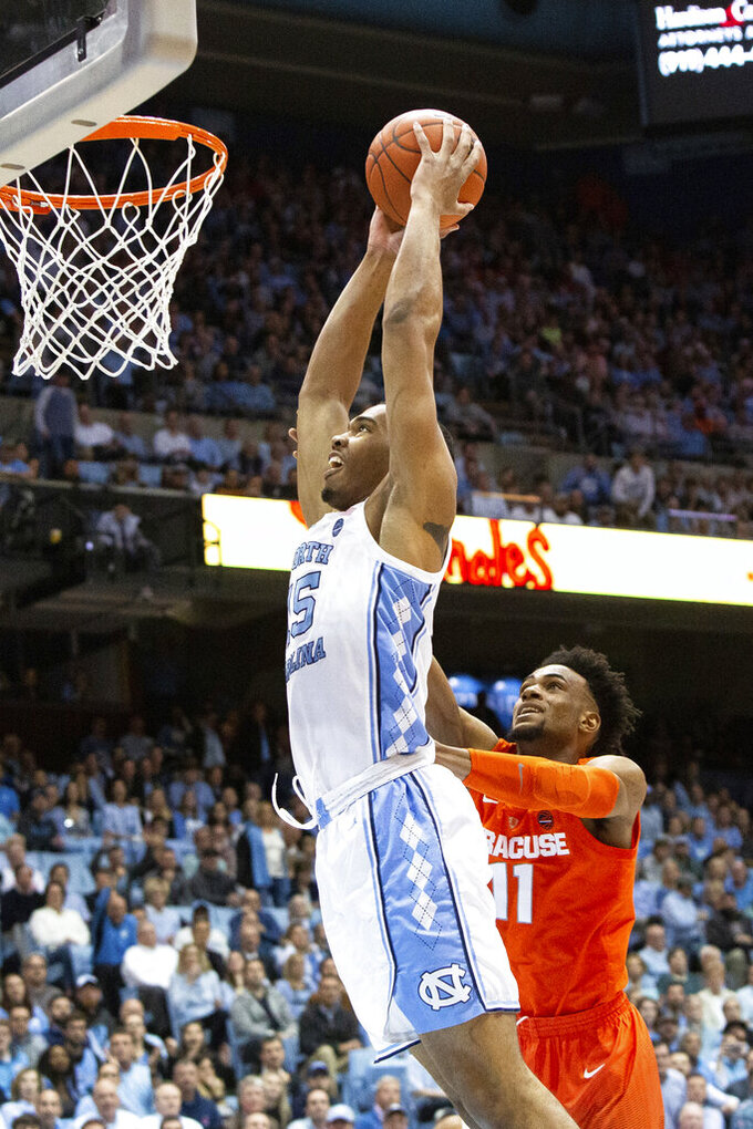North Carolina's Garrison Brooks (15) goes for a dunk on Syracuse's Oshae Brissett (11) during the first half of an NCAA college basketball game in Chapel Hill, N.C., Tuesday, Feb. 26, 2019. (AP Photo/Ben McKeown)