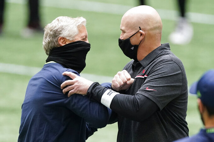Seattle Seahawks head coach Pete Carroll, left, speaks with Atlanta Falcons head coach Dan Quinn before the first half of an NFL football game, Sunday, Sept. 13, 2020, in Atlanta. (AP Photo/John Bazemore)