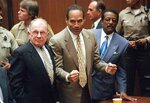 "FILE - In this Oct. 3, 1995, file photo, O.J. Simpson reacts as he is found not guilty in the death of his ex-wife Nicole Brown Simpson and her friend Ron Goldman in Los Angeles. Defense attorneys F. Lee Bailey, left, and Johnnie L. Cochran Jr. stand with him. Cochran, Simpson's flamboyant lead attorney, died of brain cancer in 2005 at 68. His refrain to jurors that ""If it doesn't fit, you must acquit"" sought to underscore that the bloody gloves found at Simpson's home and the crime scene were too small for football legend when he tried them on in court. (Myung J. Chun/Los Angeles Daily News via AP, Pool, File)"