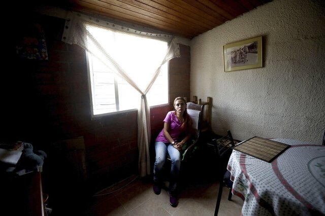 Myriam Roncancio, 35, who is living with her parents after breaking up with her husband of 10 years, sits in a chair during an interview in the Soacha borough of Bogota, Colombia, Tuesday, July 28, 2020. After she lost her job as a restaurant administrator at the start of the new coronavirus outbreak and her husband lost his as a baggage handler at Bogota's airport, they were unable to pay their rent and their quarreling became more frequent. That's when he left, she says. (AP Photo/Fernando Vergara)