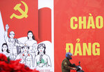 A man rides motorcycle past a poster promoting the Communist Party Congress in Hanoi, Vietnam, Saturday, Jan. 23, 2021. Almost 1,600 leading members of Vietnam's Communist Party on Tuesday, Jan. 26, 2021 begin a meeting to set policy for the next five years and select the group's senior members to steer the nation. (AP Photo/Hau Dinh)
