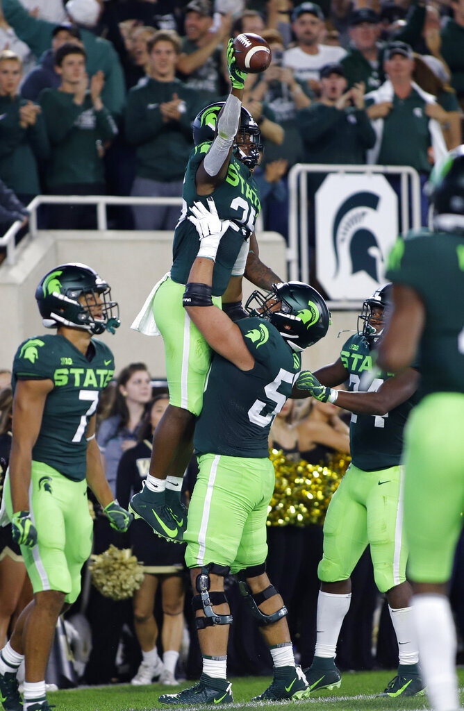 Michigan State's Darrell Stewart is lifted by Jordan Reid as they celebrate Stewart's touchdown on a pass reception against Western Michigan during the first quarter of an NCAA college football game Saturday, Sept. 7, 2019, in East Lansing, Mich. (AP Photo/Al Goldis)