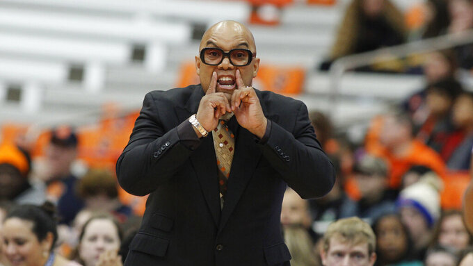 """FILE - Syracuse head coach Quentin Hillsman yells to his players in the first quarter of an NCAA college basketball game against Louisville in Syracuse, N.Y., in this Sunday, Feb. 9, 2020, file photo. Syracuse coach Quentin Hillsman has had 11 players enter the NCAA transfer portal and has brought in four players to help make up for the losses. He says the Orange are in a good place and """"not in panic mode."""" Among those who have departed are leading scorer Kiara Lewis and Emily Engstler, who led the team in rebounding as the first player off the bench. (AP Photo/Nick Lisi, File)"""