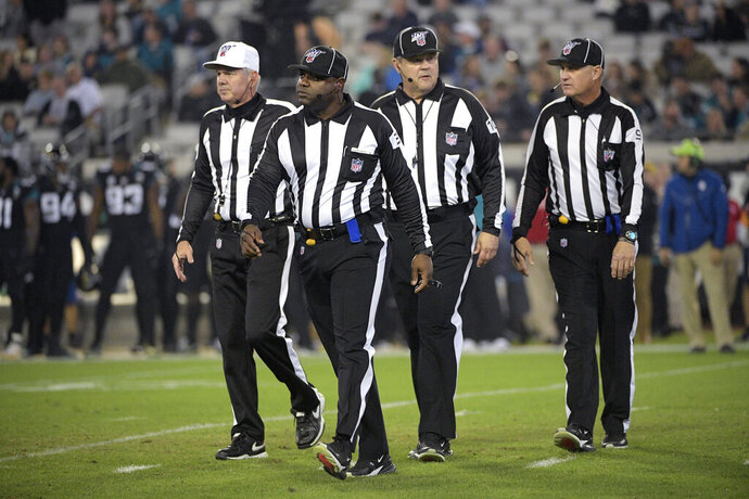 FILE - In this Dec. 8, 2019, file photo, referee Bill Vinovich, left, field judge Mearl Robinson (31), umpire Bruce Stritesky (102) and line judge Mark Perlman (9) walk to the sideline after a play during the second half of an NFL football game between the Jacksonville Jaguars and the Los Angeles Chargers, in Jacksonville, Fla. Save the outrage for something else. NFL officiating won't get any better this weekend, or anytime soon _ because it can't. (AP Photo/Phelan M. Ebenhack, File)
