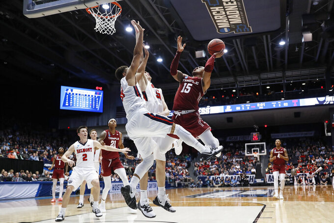 Temple's Nate Pierre-Louis (15) shoots against Belmont's Seth Adelsperger, center, and Kevin McClain, center left, during the second half of a First Four game of the NCAA college basketball tournament, Tuesday, March 19, 2019, in Dayton, Ohio. (AP Photo/John Minchillo)