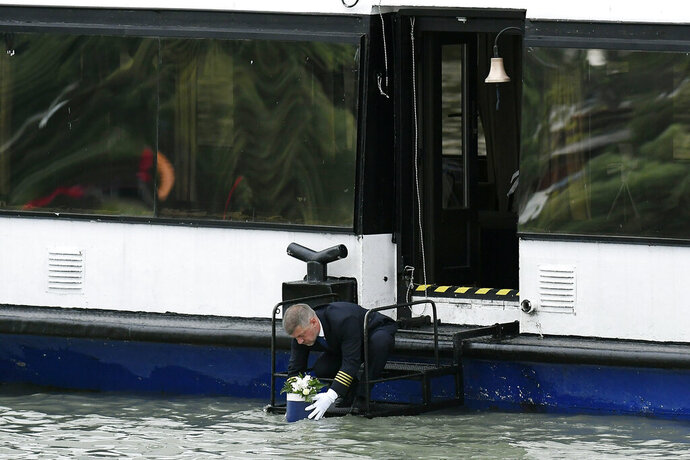 The urn containing the ashes of the sailor of the sunken boat is placed from a ship into River Danube by a ship's captain during the funeral ceremony of the two Hungarian victims of the boat accident last May in Budapest, Hungary, Friday, July 12, 2019. They were the two crew members of a tourist boat carrying 33 South Korean tourists that was crashed by a large river cruise ship and sank in River Danube at a pier of Margaret Bridge in Budapest on May 29, killing 28 people. The remains of the captain of the boat will be buried on the land later. Seven Korean tourists survived the accident. (Szilard Koszticsak/MTI via AP)