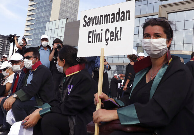 Lawyers wearing face masks to protect against the spread of coronavirus, as one holds a placard that reads
