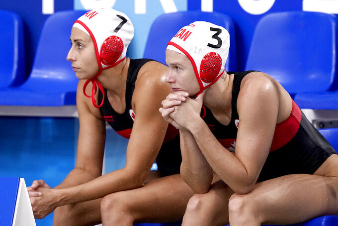 Canada's Joelle Bekhazi (7) and Axelle Crevier (3) sit on the bench during the final moments of a loss to the United States in a quarterfinal round women's water polo match at the 2020 Summer Olympics, Tuesday, Aug. 3, 2021, in Tokyo, Japan. (AP Photo/Mark Humphrey)
