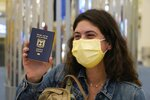 FILE - In this Nov. 26, 2020 file photo, an Israeli passenger from a flyDubai flight from Tel Aviv, Israel, waves her Israeli passport on arrival at Dubai International Airport's Terminal 3 in Dubai, United Arab Emirates. Travel agencies in countries across the Middle East and Africa say the United Arab Emirates has temporarily halted issuing new visas to their citizens, a so-far unexplained ban on visitors amid both the coronavirus pandemic and as the UAE normalizes ties with Israel. (AP Photo/Jon Gambrell, File)