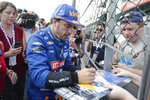 Fernando Alonso, of Spain, stops to sign autographs after qualifications ended for the Indianapolis 500 IndyCar auto race at Indianapolis Motor Speedway, Saturday, May 18, 2019, in Indianapolis. (AP Photo/Michael Conroy)