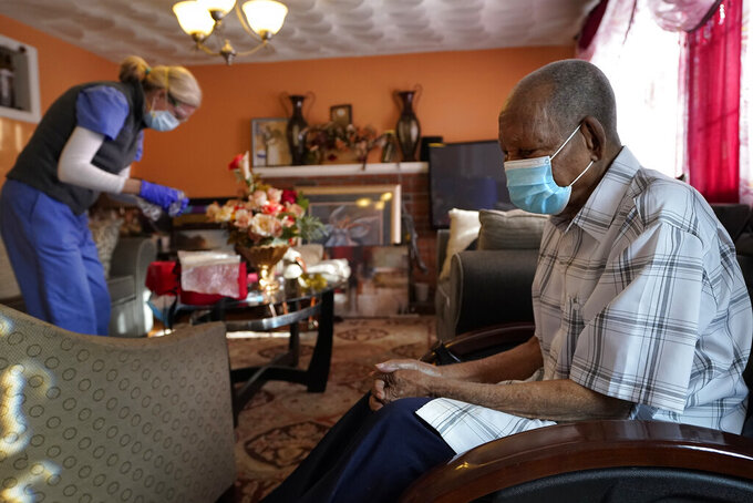 FILE - In this Feb. 11, 2021, file photo Edouard Joseph, 91, right, clasps his hands as geriatrician Megan Young, left, prepares to give him a COVID-19 vaccination at his home in the Mattapan neighborhood of Boston. A majority of Americans agree that government should help people fulfill a widely held aspiration to age in their own homes, not institutional settings, according to a new survey from The Associated Press-NORC Center for Public Affairs Research. (AP Photo/Steven Senne, File)