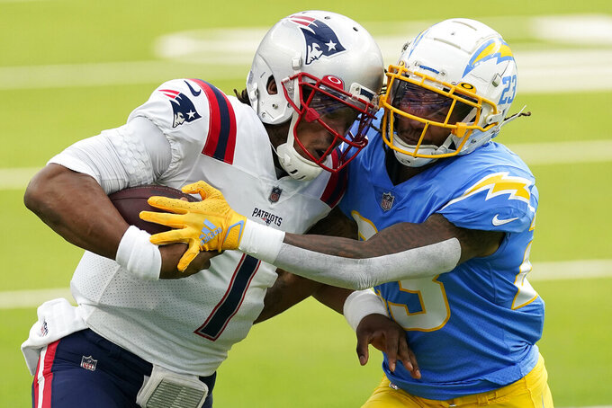 New England Patriots quarterback Cam Newton, left, is tackled by Los Angeles Chargers strong safety Rayshawn Jenkins during the first half of an NFL football game Sunday, Dec. 6, 2020, in Inglewood, Calif. (AP Photo/Ashley Landis)
