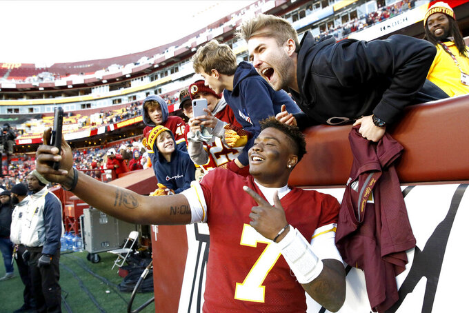 Washington Redskins quarterback Dwayne Haskins takes selfies with fans during the second half of an NFL football game against the Detroit Lions, Sunday, Nov. 24, 2019, in Landover, Md. The Redskins won 19-16. (AP Photo/Patrick Semansky)