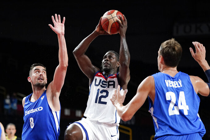 United States's Jrue Holiday (12) drives to the basket between the Czech Republic's Tomas Satoransky (8) and Jan Vesely (24) during a men's basketball preliminary round game at the 2020 Summer Olympics, Saturday, July 31, 2021, in Saitama, Japan. (AP Photo/Charlie Neibergall)