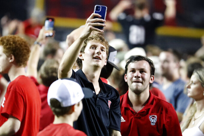 North Carolina State fans take a photo on the field following a win over Clemson in double overtime of an NCAA college football game in Raleigh, N.C., Saturday, Sept. 25, 2021. (AP Photo/Karl B DeBlaker)