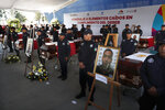 Michoacan state police stand next to the coffins of slain colleagues during a memorial service at the public security department headquarters for Michoacan, in Morelia, Mexico, Tuesday, Oct. 15, 2019. More than 30 suspected cartel gunmen ambushed the police officers in the town of El Aguaje on Monday as they were traveling in a convoy to serve a warrant, killing 13 officers and wounding nine others. (AP Photo/Marco Ugarte)