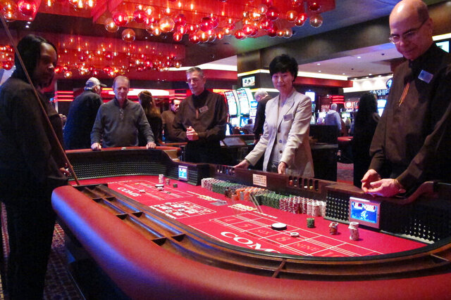 In this Feb. 22, 2019 photo, players gather around a table of craps at the Golden Nugget casino in Atlantic City N.J. Commercial casinos in 25 U.S. states won $43.6 billion from gamblers in 2019, an increase of nearly 4% from the previous year, according to a report issued late Wednesday, June 3, 2020, by The American Gaming Association, the casino industry's national trade group. (AP Photo/Wayne Parry)