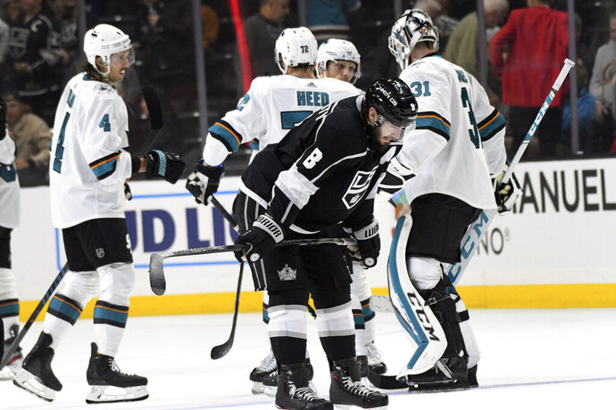 Los Angeles Kings defenseman Drew Doughty, front, looks down as San Jose Sharks defenseman Brenden Dillon, left, defenseman Tim Heed, center, and goalie Martin Jones (31) celebrate their 4-3 win in overtime of an NHL hockey game, Monday, Nov. 25, 2019, in Los Angeles. (AP Photo/Michael Owen Baker)