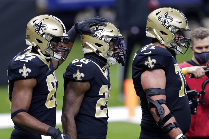 New Orleans Saints running back Latavius Murray (28) is congratulated by tight end Jared Cook (87) and offensive tackle Ryan Ramczyk (71) after his touchdown reception in the second half of an NFL wild-card playoff football game against the Chicago Bears in New Orleans, Sunday, Jan. 10, 2021. (AP Photo/Brett Duke)