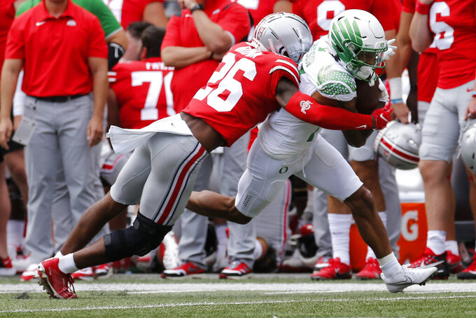 Ohio State defensive back Cameron Brown, left, tackles Oregon receiver Kris Hutson during the first half of an NCAA college football game Saturday, Sept. 11, 2021, in Columbus, Ohio. Oregon beat Ohio State 35-28. (AP Photo/Jay LaPrete)