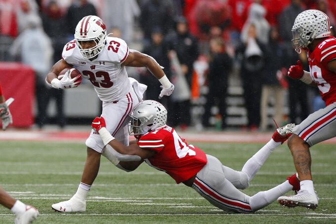 Wisconsin running back Jonathan Taylor, left, tries to cut up field past Ohio State linebacker Justin Hilliard during the first half of an NCAA college football game Saturday, Oct. 26, 2019, in Columbus, Ohio. (AP Photo/Jay LaPrete)