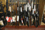 In this Monday, Nov. 4, 2019 photo, long guns fill a rack in an evidence room at the Toledo Police Department in Toledo, Ohio. In the basement of the Toledo Police Department, more than 20,000 items collected from crime scenes across the city each year are stored to help verify what happened or to be used to find and convict suspects. (Andy Morrison/The Blade via AP)