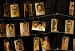 """FILE - In this Friday, April 5, 2019 file photo, family photographs of some of those who died hang on display in an exhibition at the Kigali Genocide Memorial centre in the capital Kigali, Rwanda. A commission that spent nearly two years uncovering France's role in 1994's Rwandan genocide concluded Friday, March 26, 2021 that the country reacted too slowly in appreciating the extent of the horror that left over 800,000 dead and bears """"heavy and overwhelming responsibilities"""" in the drift that led to the killings, but cleared the country of any complicity in the slaughter that mainly targeted Rwanda's Tutsi ethnic minority. (AP Photo/Ben Curtis, File)"""