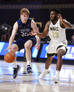 Longwood's Jesper Granlund is pressured by Wake Forest's Isaiah Wilkins during the first half of an NCAA basketball game Friday, Nov. 27, 2020, in Winston-Salem, N.C. (Walt Unks/The Winston-Salem Journal via AP, Pool)
