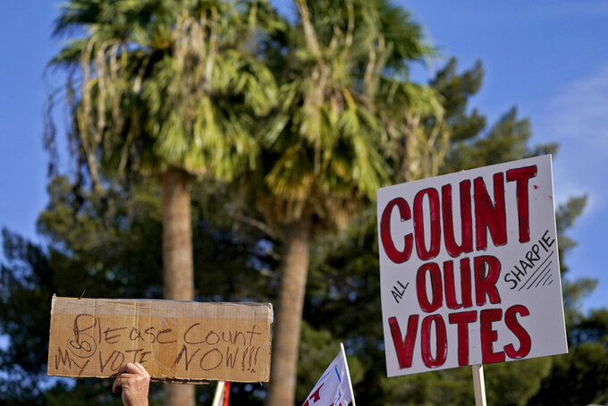 Protesters hold signs during an Arizona Republican Party news conference, Thursday, Nov. 5, 2020, in Phoenix. (AP Photo/Matt York)