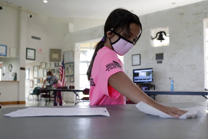 Valentina Fasano cleans her work space with sanitizing wipes at the Girl's Empowerment and Mentoring (G.E.M.) Summer Arts Camp during the coronavirus pandemic, Wednesday, July 15, 2020, in Miami. This Miami-Dade County summer camp program is operating at limited capacity, and has enhanced health screening and sanitizing procedures, practices social distancing, and required wearing of face coverings. (AP Photo/Lynne Sladky)