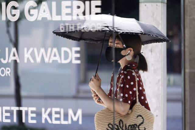 A woman wearing a protective mask to help curb the spread of the new coronavirus is reflected on a mirror window of a shop Wednesday, Aug. 12, 2020, in Tokyo. Hot weather Wednesday has set with temperatures rising up over 34 degrees Celsius (93.2 degrees Fahrenheit) in Tokyo, according to the Japan Meteorological Agency. (AP Photo/Eugene Hoshiko)
