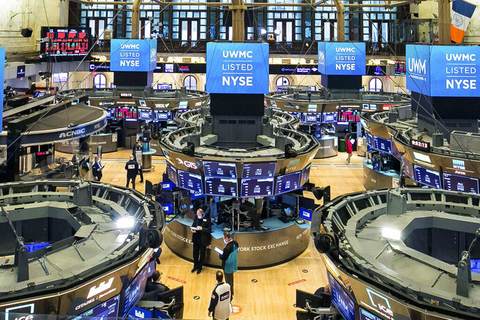 In this photo provided by the New York Stock Exchange, traders work on the floor during the United Wholesale Mortgage IPO, Friday, Jan. 22, 2021. Wall Street is tapping the brakes on its record-setting rally this week, as markets worldwide take a pause on Friday. (Courtney Crow/New York Stock Exchange via AP)