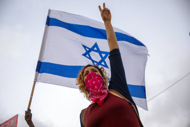 Israeli protesters wave flags and chant slogans during a demonstration against parliament's plans to ban them from protesting during the current nationwide lockdown due to the coronavirus pandemic, in Tel Aviv, Israel, Tuesday, Sept. 29, 2020. The protesters accuse Prime Minister Benjamin Netanyahu of exploiting the coronavirus crisis in order to stop weeks of demonstrations against him. (AP Photo/Oded Balilty)