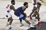 Villanova's Justin Moore, center, keeps the ball from Hartford's Traci Carter, left, and Austin Williams, right, in the second half of an NCAA college basketball game Tuesday, Dec. 1, 2020, in Uncasville, Conn. (AP Photo/Jessica Hill)