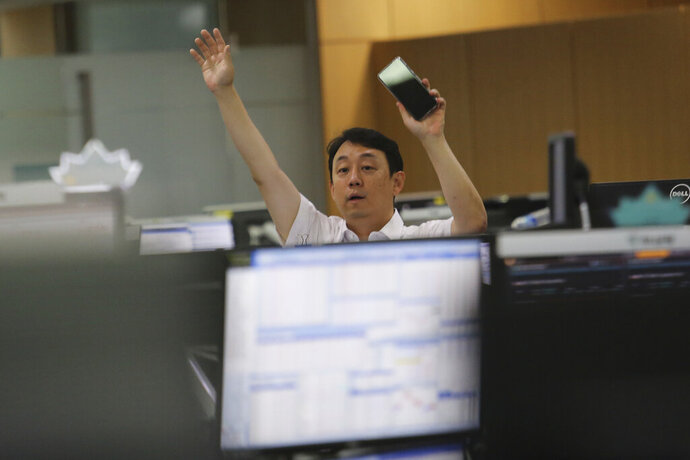 A currency trader gestures at the foreign exchange dealing room of the KEB Hana Bank headquarters in Seoul, South Korea, Thursday, July 9, 2020. Asian stock markets followed Wall Street higher on Thursday following gains for major U.S. tech stocks. (AP Photo/Ahn Young-joon)